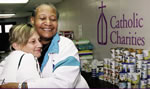 Catholic Charities voluteers hand out hugs and canned goods